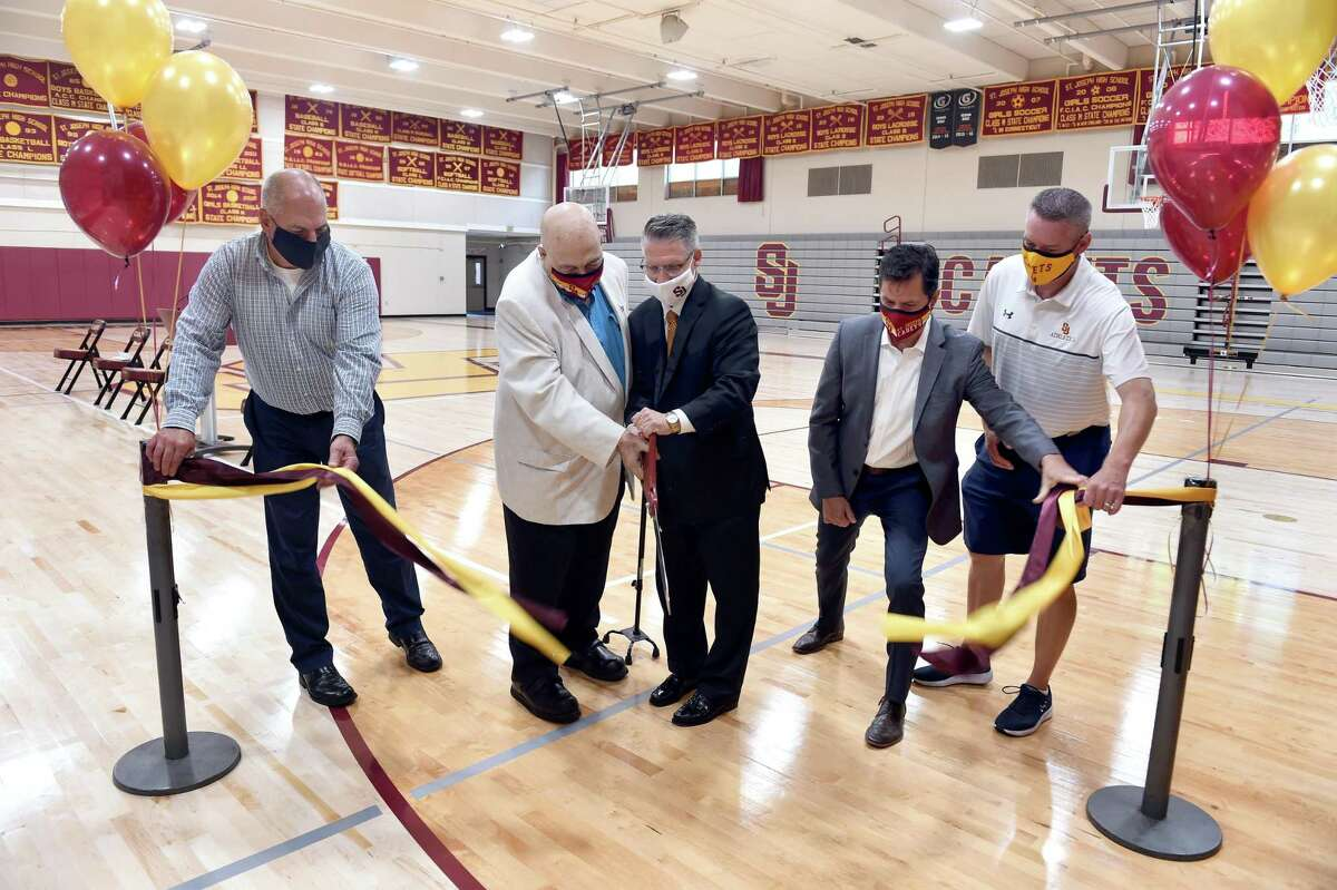 Former basketball coach Vito Montelli, left center, and David Klein, right center, President of St. Joseph High School, cut the ribbon at the renovated St. Joseph High School gym rededicated in honor of Montelli in August.