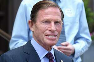 In a file photo, New Haven Mayor Justin Elicker (background) listened to U.S. Senator Richard Blumenthal during a news conference in front of City Hall.