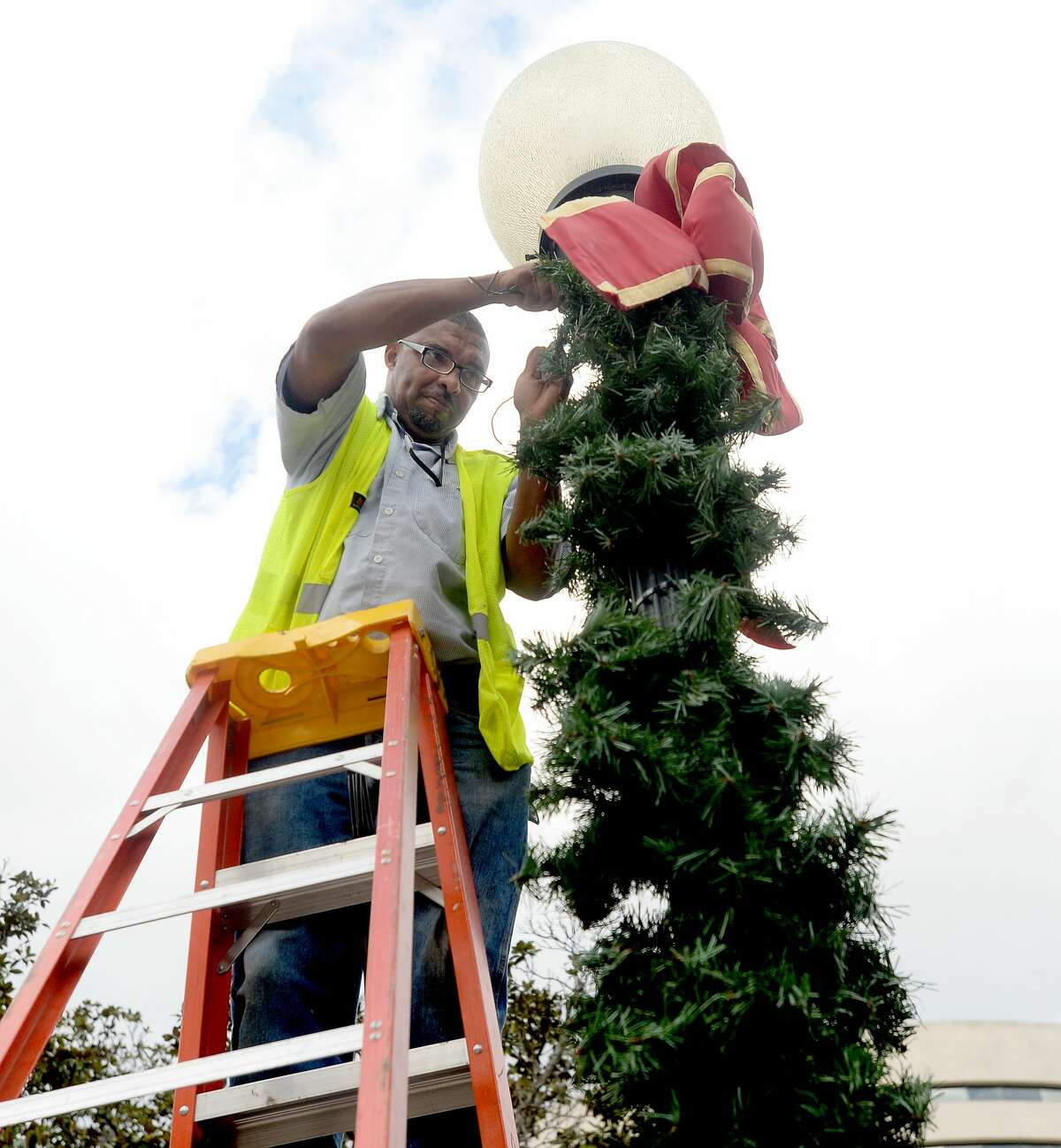 City of Beaumont workers Tim Cole and Steve Moore (not pictured) team up to decorate the light poles lining Main Street as holiday decorating throughout downtown got underway Monday. Throughout the week, city workers will hang banners, more lights and garland, and Thursday put up the city Christmas tree at the Event Centre. Photo taken Monday, November 9, 2020 Kim Brent/The Enterprise