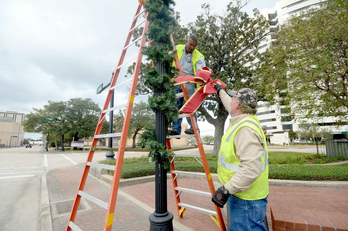 City of Beaumont workers Tim Cole and Steve Moore team up to decorate the light poles lining Main Street as holiday decorating throughout downtown got underway Monday. Throughout the week, city workers will hang banners, more lights and garland, and Thursday put up the city Christmas tree at the Event Centre. Photo taken Monday, November 9, 2020 Kim Brent/The Enterprise