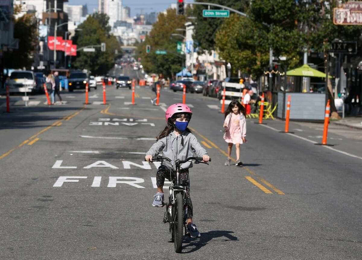 Sofia Manzari, 11, pedals and her sister Nina, 6, walks on a vehicle-free block of Valencia Street.