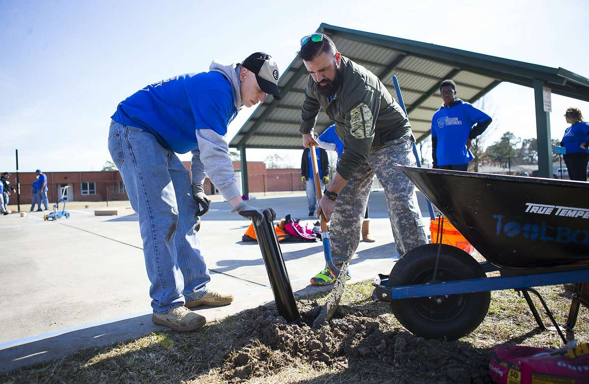 Raul Talavera (right), a U.S. Army combat veteran, assembles a basketball hoop at Roderick Paige Elementary School in the Kashmere Gardens community during a day of service with the organization The Mission Continues, Monday, Jan. 15, 2018, in Houston. The Mission Continues is a veteran-led, nationwide service organization that deployed around 200 volunteers at the elementary school on Monday. The organization has five platoons in the Houston area that perform service projects year round. ( Mark Mulligan / Houston Chronicle )