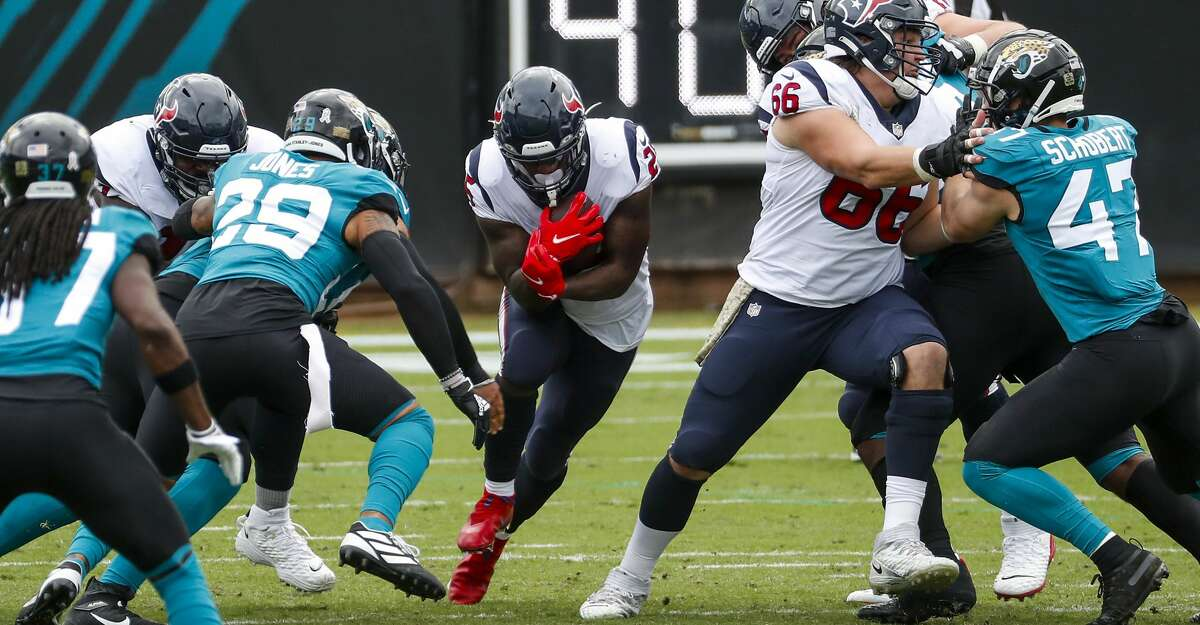Houston Texans running back Duke Johnson (25) runs the ball through a small hole against the Jacksonville Jaguars during the first half of an NFL football game at TIAA Bank Field Sunday, Nov. 8, 2020, in Jacksonville.