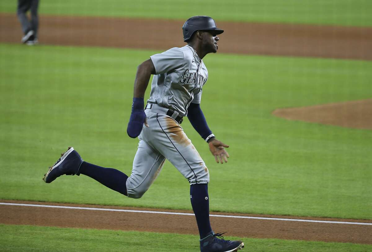 Seattle Mariners right fielder Kyle Lewis (1) goes home and scores during the first inning of a MLB game against the Houston Astros Sunday, July 26, 2020, at Minute Maid Park in Houston.