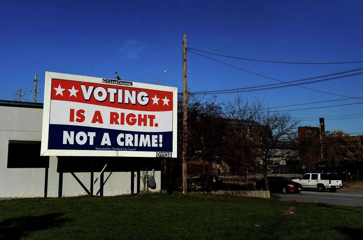 """CLEVELAND, OH - OCTOBER 28: A billboard company, Clear Channel Outdoor, last week took down 30 billboards in inner-city Cleveland that critics say were attempts to intimidate minority voters. The billboards featured a judge's gavel and the huge words """"Voter Fraud Is A Felony! Up to 3 ½ years $ $10,000 fine."""" It was reported that the company did not identify who paid for the billboards and acknowledged that it was a mistake to agree to the contract. Still in places are these billboards with a counter-message: """"Voting Is a Right, Not a Crime!"""" Cities along Lake Erie from Toledo to Cleveland feature union workers, urban dwellers and younger people who have been steady Democratic voters. Some consider this part of the state a stronghold for the President. (Photo by Michael S. Williamson/The Washington Post via Getty Images"""
