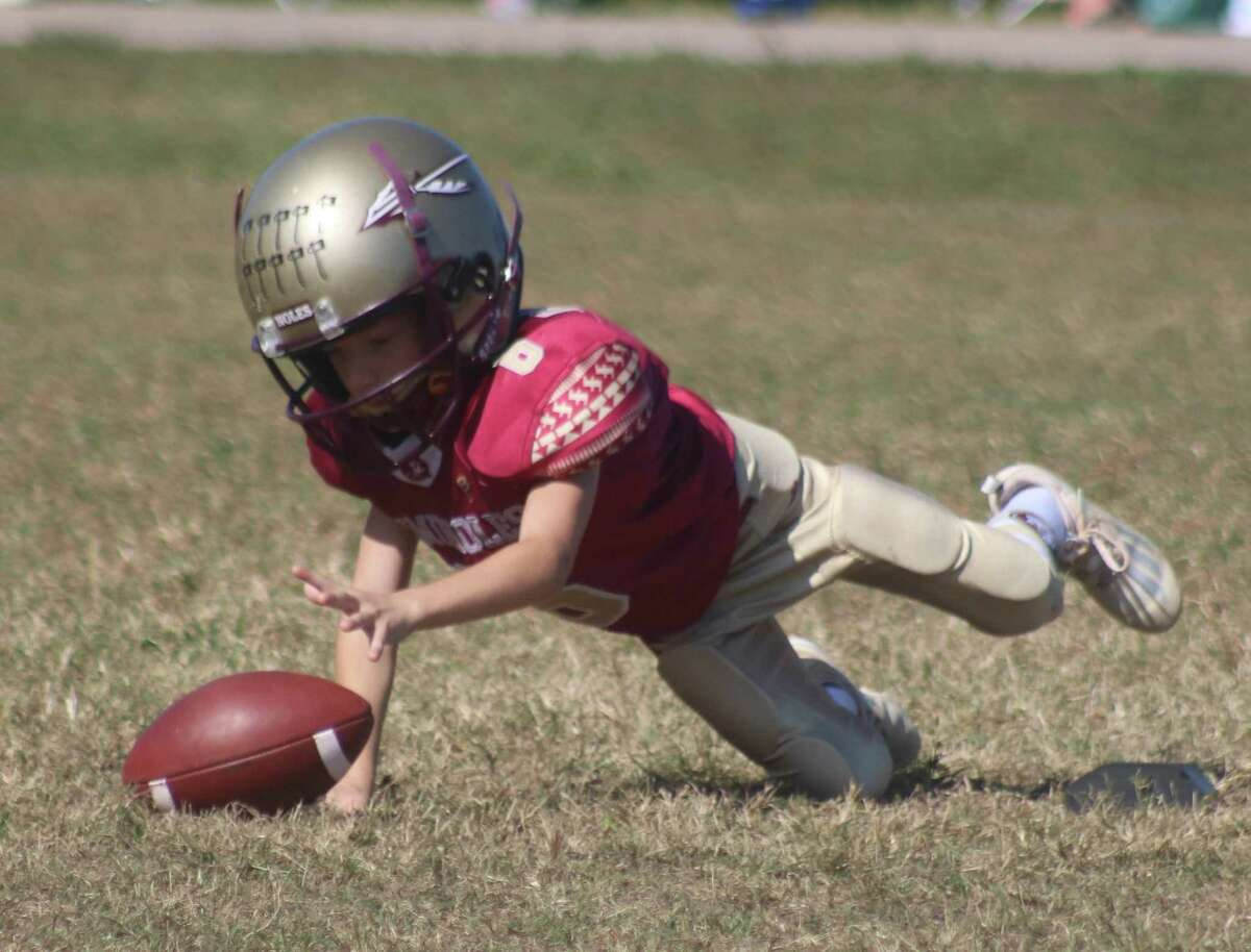 So thankful that there's no rush in TIFI games for extra point attempts, Deer Park Freshmen Seminoles holder Connor Deason retrieves a bad snap during Saturday's game at Centennial Park.