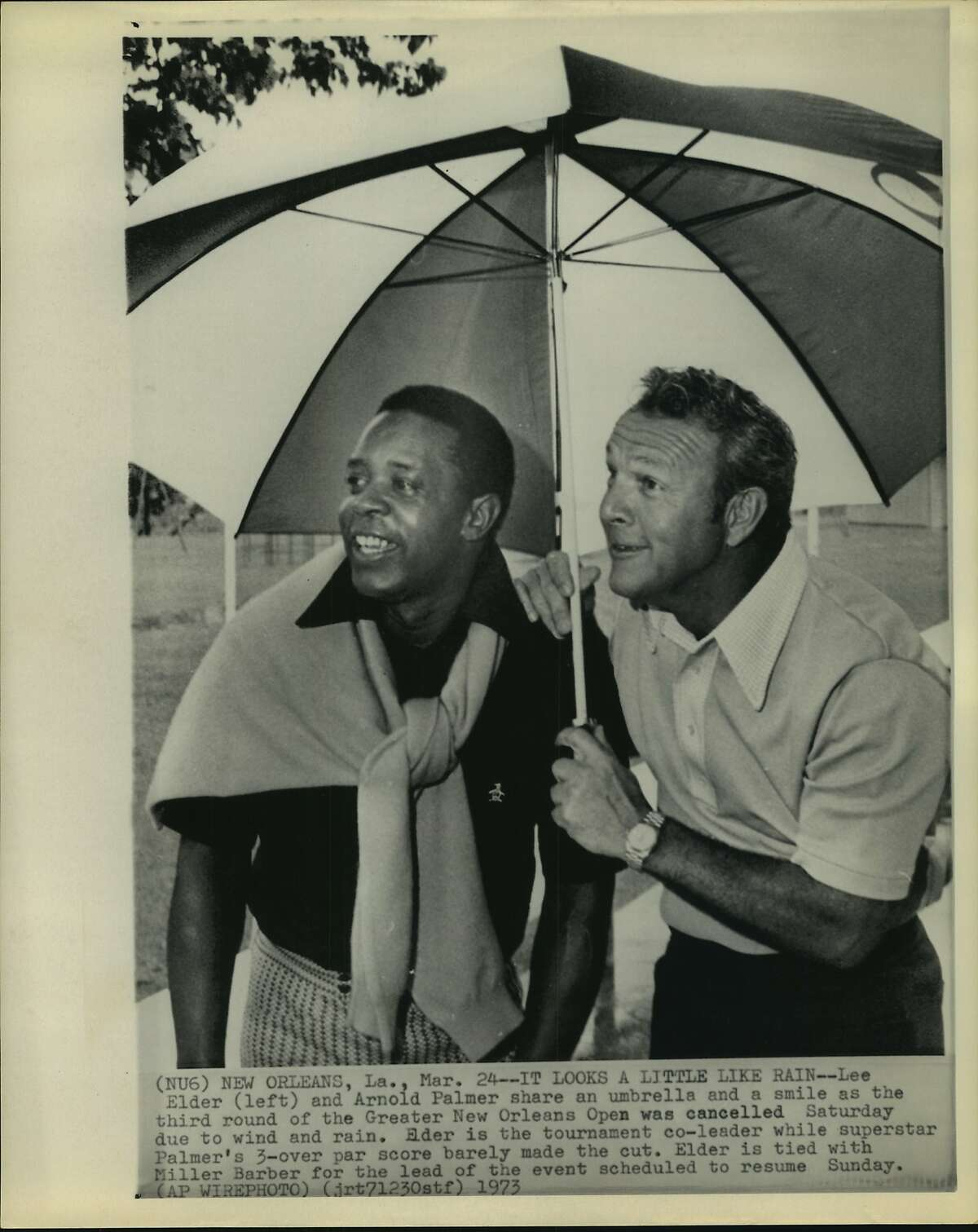 Lee Elder (left) and Arnold Palmer share an umbrella and a smile as the third round of the Greater New Orleans Open was canceled Saturday due to wind and rain.