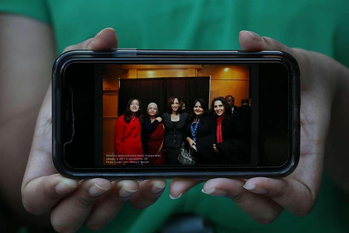 Avani Hamilton holds a 2011 photo of herself (left); grandmother Anuradha Bakshi; Kamala Harris; Shikha Hamilton; and aunt Nikki Arora, taken during Harris' inauguration for California attorney general.