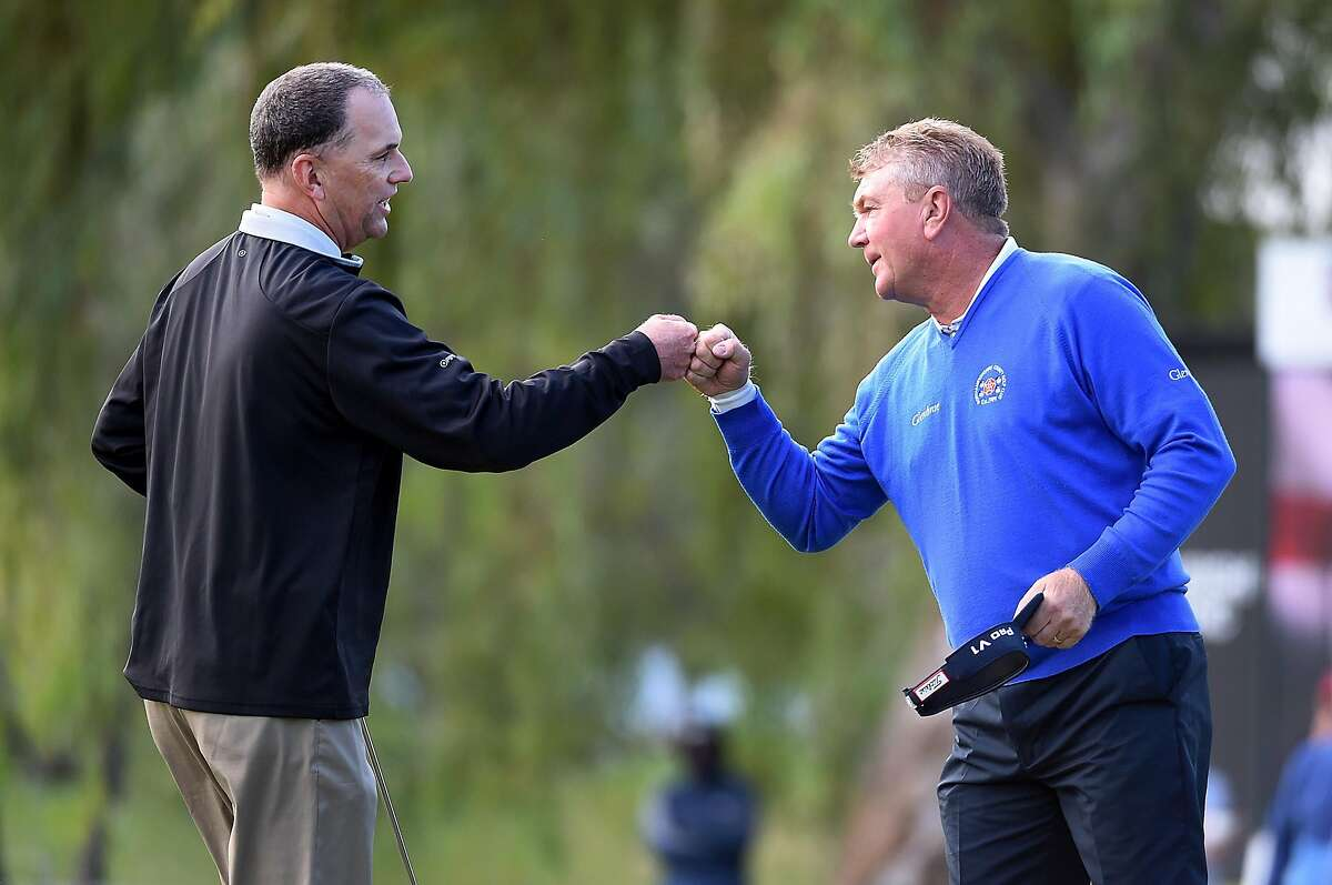 Kevin Suther- land (left) fist bumps Paul Broad- hurst after prevailing in a nine-hole playoff to win the Charles Schwab Cup Champ- ionship.