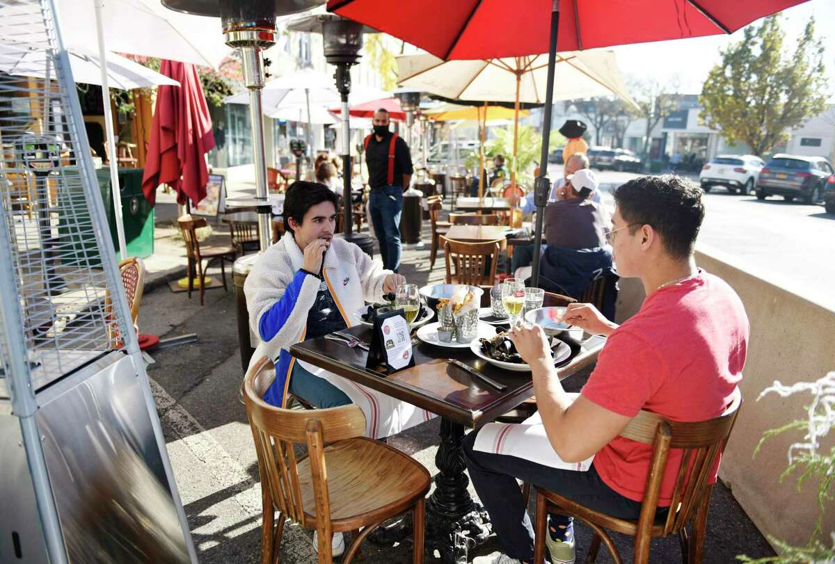 Greenwich's Charlie-Andre Jolly, left, and Brentwood, N.Y.'s Brian Torres dine outdoors at Bistro V in Greenwich, Conn. Monday, Nov. 9, 2020. First Selectman Fred Camillo said outdoor dining is here to stay and focus continues on how to balance this with parking needs.