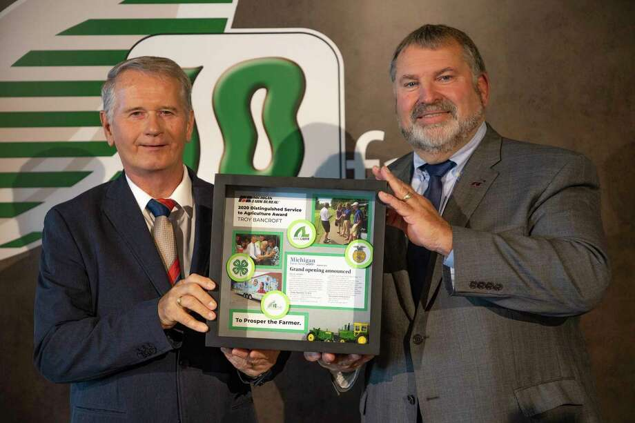 Michigan Farm Bureau President Carl Bednarski (right) presents Troy Bancroft with a shadow box of images in honor of him being named recipient of MFB's Distinguished Service to Agriculture Award during the organization's 101st annual meeting. (Michigan Farm Bureau/Courtesy Photo)
