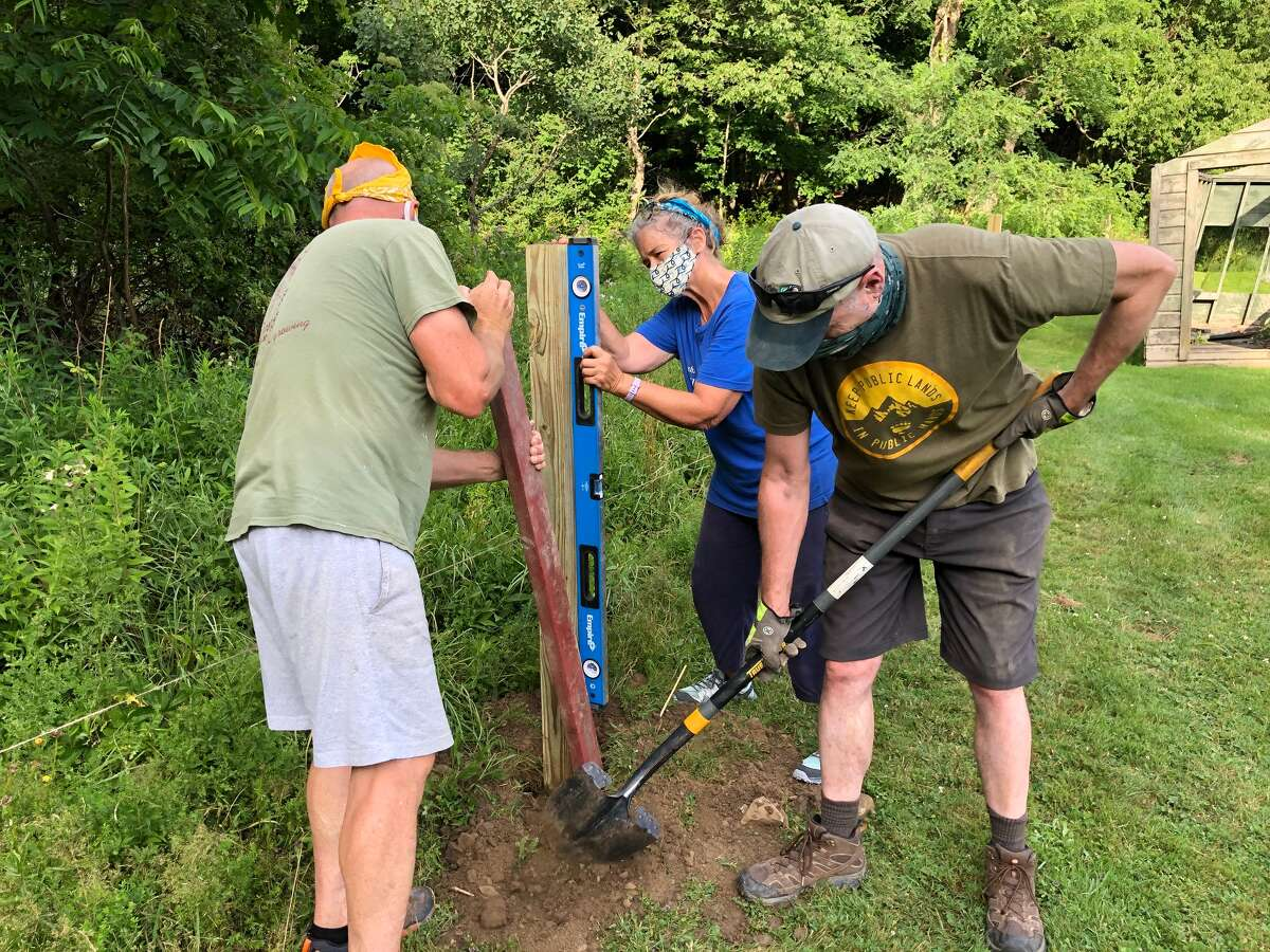 Tim Lippert, left, Joe Frisino, right, and Judy Crilley, center, work on putting up a post for a StoryWalk trail.