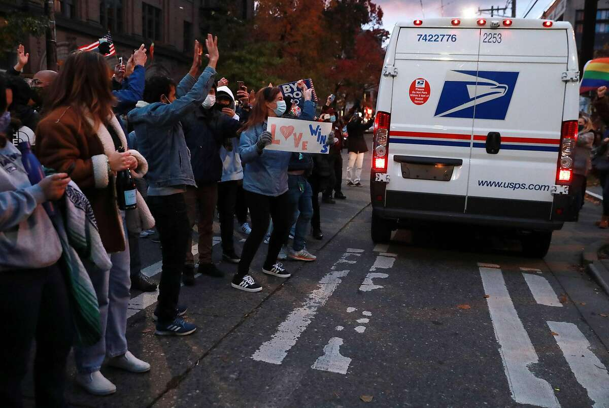 Crowds in Seattle cheer as a U.S. Postal Service vehicle passes during celebrations after Democratic nominee Joe Biden is announced as the winner of the presidential election Saturday.