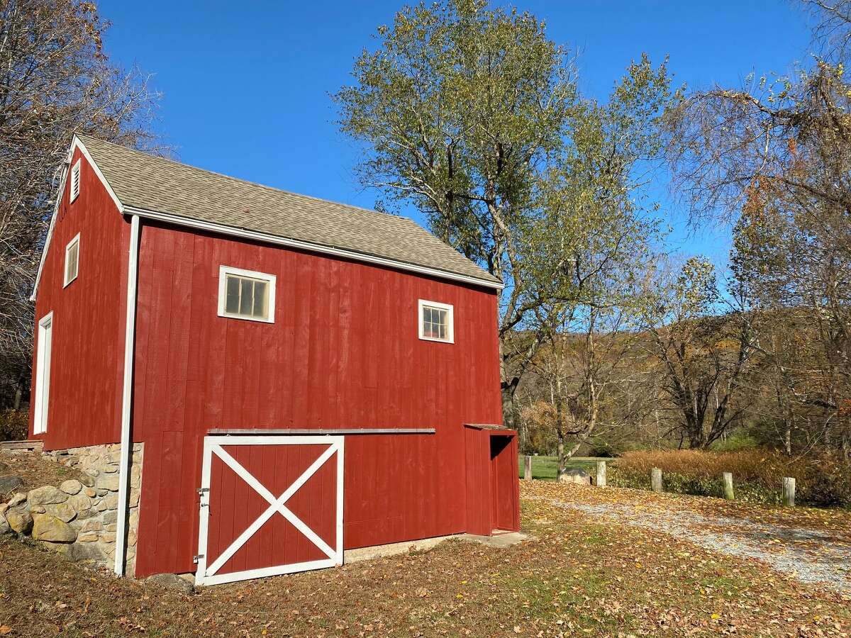 The barn at Clatter Valley Farm creates a striking image against the green trees at the park off Clatter Valley Farm Road.