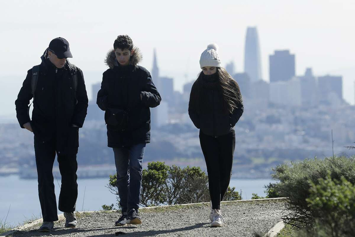 In this file photo, a family dressed for cold weather walks down a path in front of the San Francisco skyline near Sausalito, California.