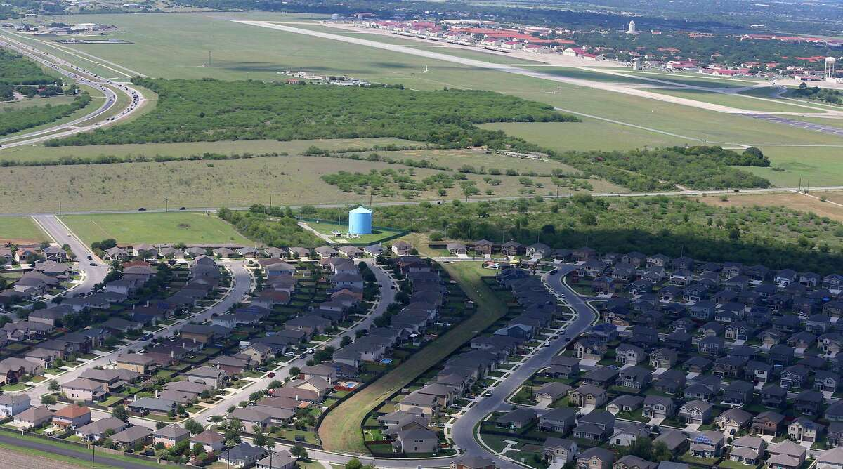 This is one location of suburban expansion east of Joint Base San Antonio-Randolph, shown in 2017. Housing developments (bottom) are being built near areas called APZs, or Accident Potential Zones. A water tower and the landmark Randolph building known as the