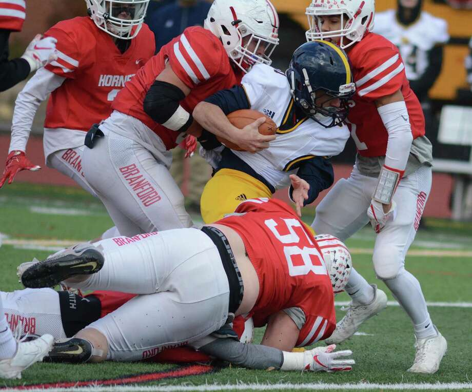 East Haven's Eric Araujo is stopped by three Branford defenders during a football game against Branford on Thanksgiving morning, Nov. 28, 2019, in Branford, Conn. Photo: Dave Phillips / For Hearst Connecticut Media / Stamford Advocate Freelance