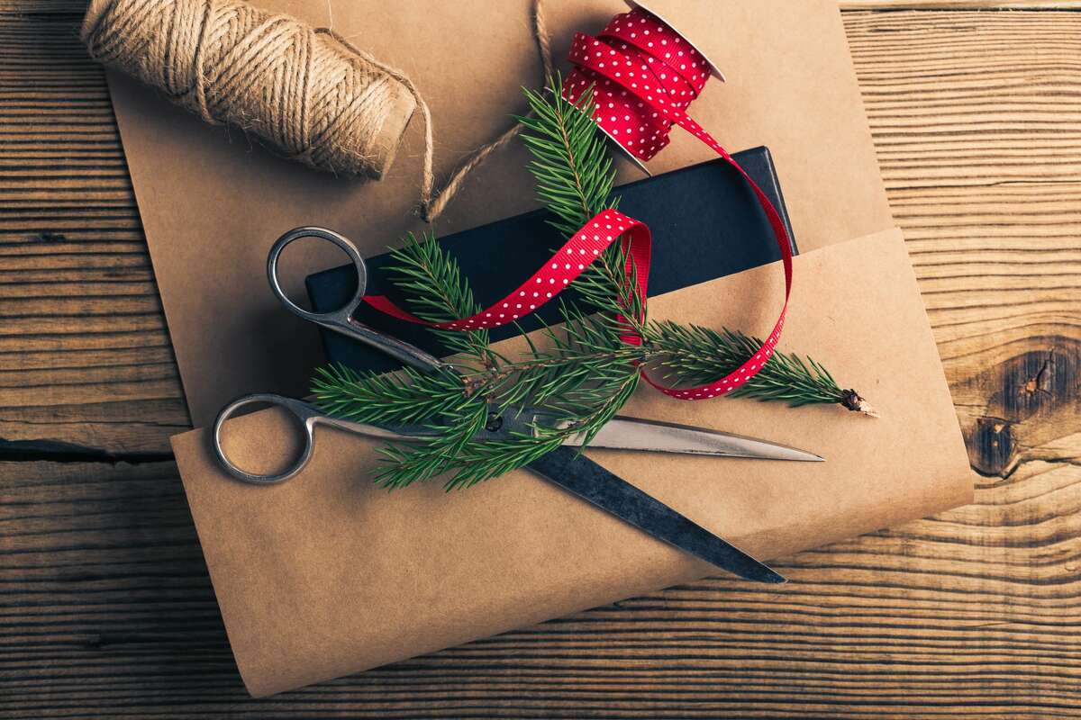 Wrap Christmas gifts in brown paper bags and accessorize with a burlap twine, ribbon and a sprig of greenery for a trendy, farmhouse look.