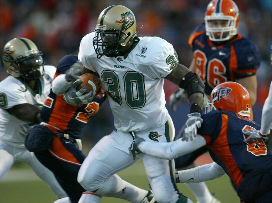 UAB running back Corey White (30) runs for a first down as Texas-El Paso defenders Quintin Demps, right, and Josh Ferguson, left, attempt to tackle him during the second quarter Saturday, Nov. 19, 2005, in El Paso, Texas. (AP Photo/Victor Calzada) Photo: VICTOR CALZADA/AP