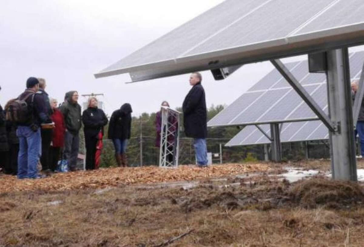 Mark Fobare, background center, CEO of Monolith Solar, addresses those gathered for a Monolith Solar ribbon cutting event at their first Community Solar farm on Wednesday, March 29, 2017, in Johnsonville, N.Y.