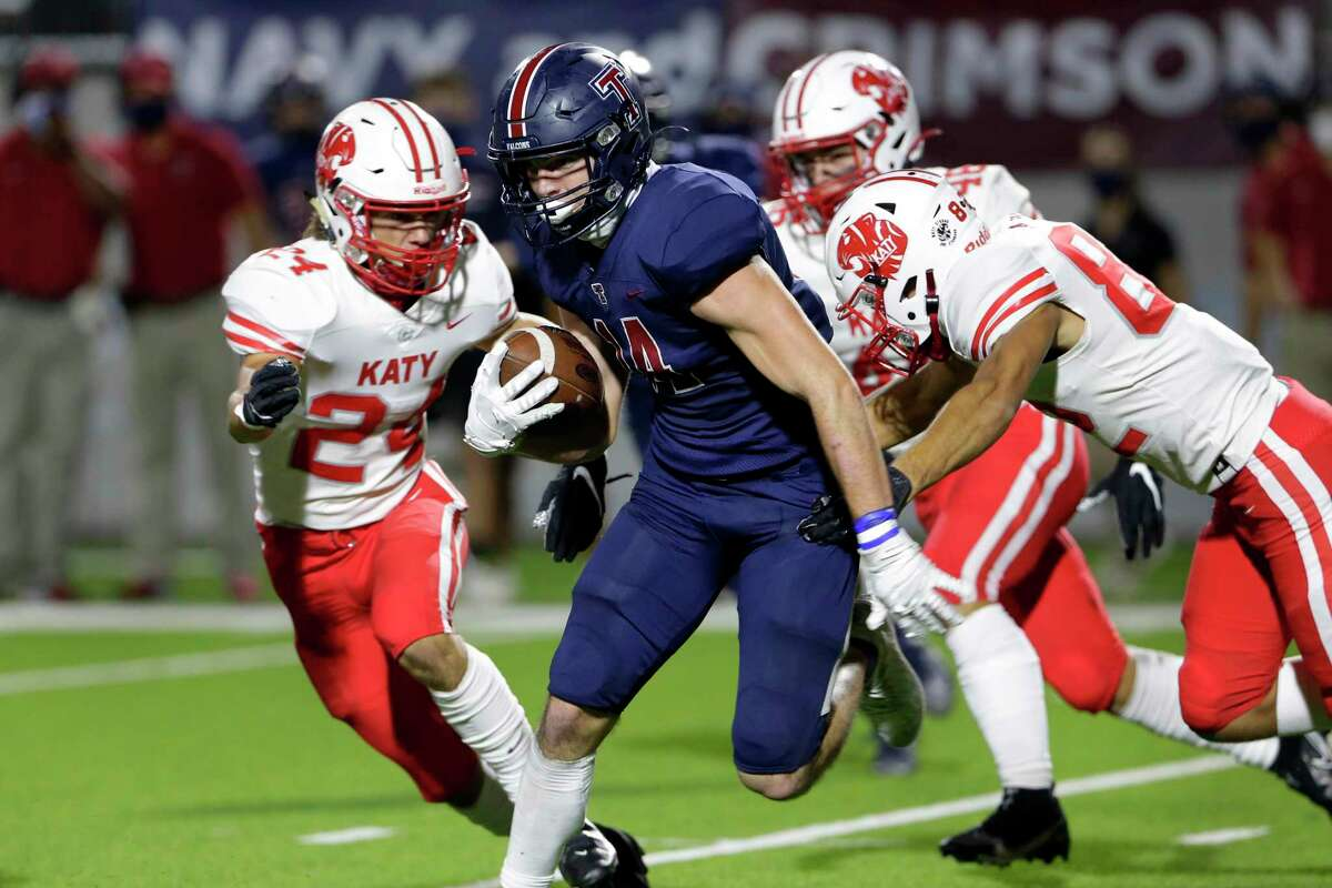 Tompkins Colby Huerter (14) makes a gain between Katy defenders Hamilton McMartin (24) and Antonio Silva, right, during the first half of a high school football game at Legacy Stadium Thursday, Nov. 5, 2020 in Katy, TX.