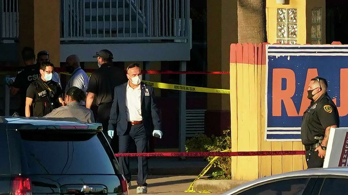 Police personnel and others are shown outside the Taj Inn and Suites, 7766 North Fwy., where a Houston Police Dept. sergeant was fatally shot, according to police officials, Monday, Nov. 9, 2020 in Houston.