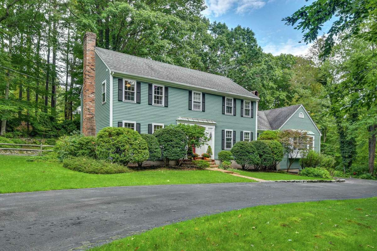 The green colonial house at 261 Hemlock Hills Road South in Fairfield's Greenfield Hill neighborhood sits on a 3.44-acre level and lightly wooded parcel.