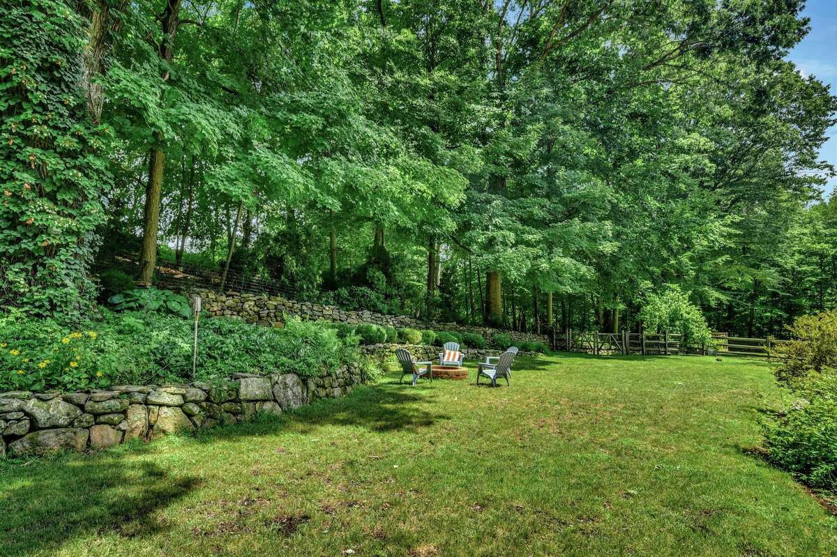 The backyard has a fire pit, attractive gardens and stone walls.