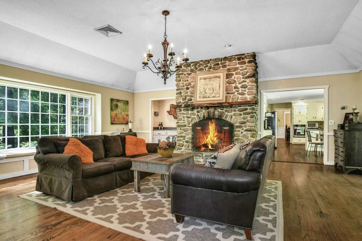 The family room features a floor-to-ceiling stone fireplace as well as a wet bar, tray ceiling, and French doors to the deck.