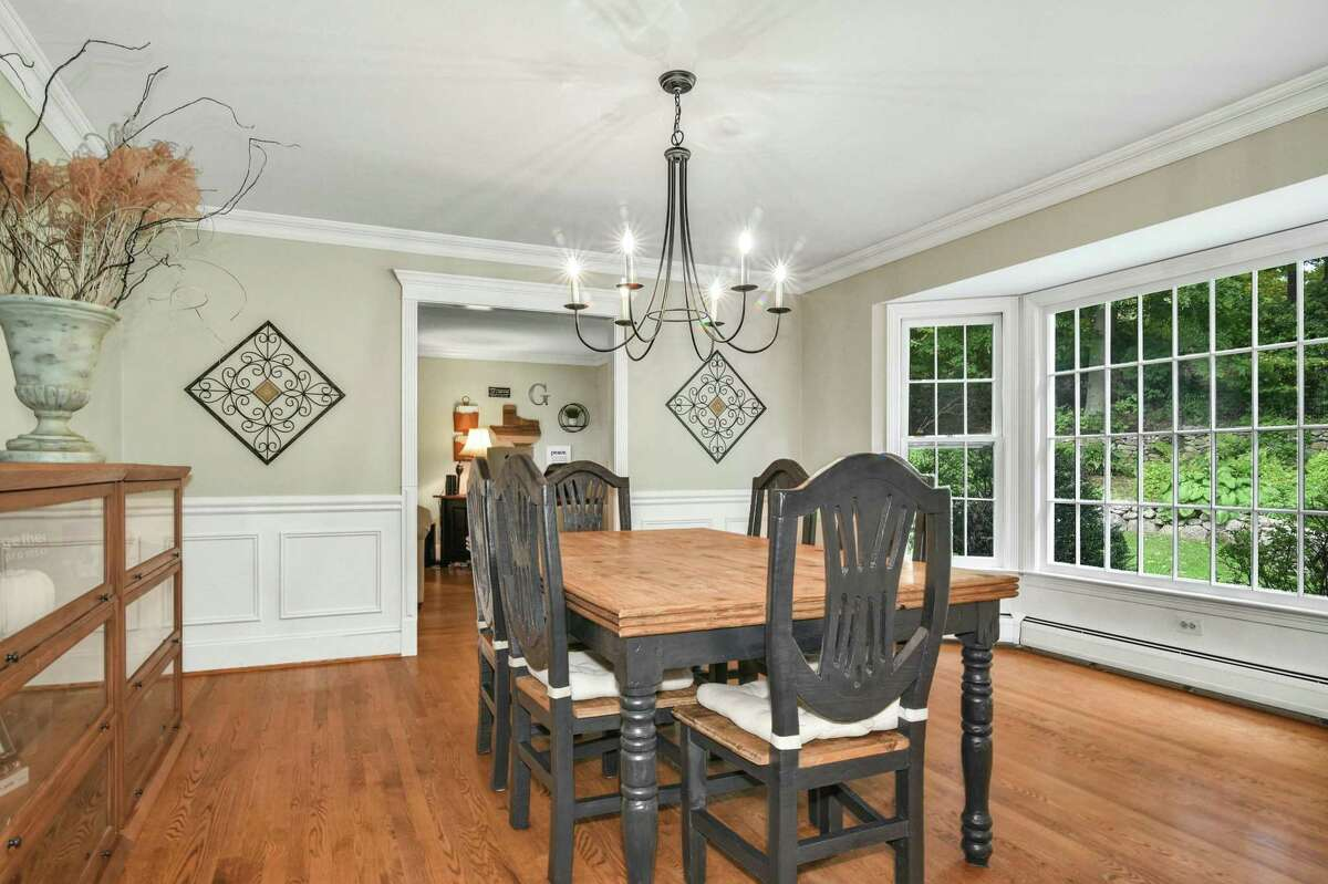The formal dining room has a large bay window and wainscoting on the lower walls.