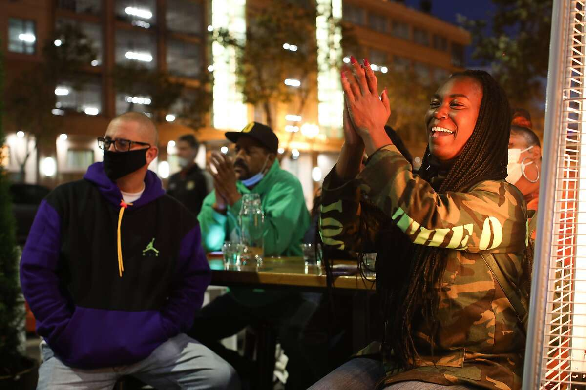 Quiana Easter, right, who recently moved from Oakland to Pittsburg, sits at the Oakland Athletic Club as she watches Vice President-elect Kamala Harris as she delivers her victory speech on Saturday, November 7, 2020, in Oakland, Calif.
