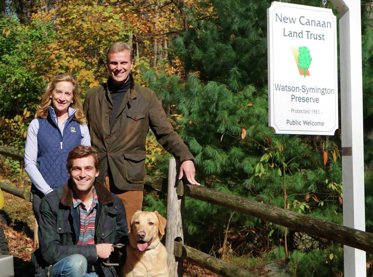 Gina and Dennis Podlesak, with their son Justin (one of the New Canaan Land Trust's first summer stewards) and their dog Red, with one of the new signs identifying Land Trust property. The Land Trust has new signage at the entrances of eight of its most popular preserves.