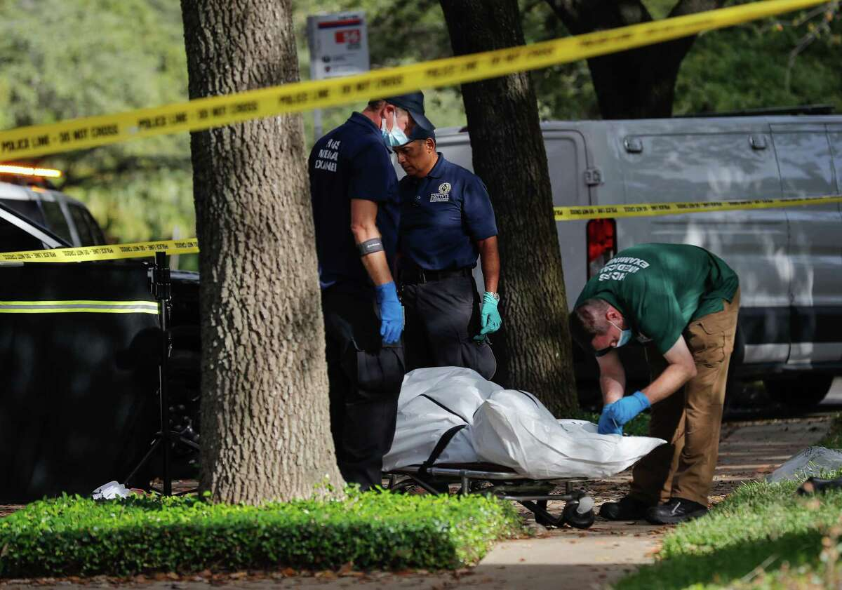 Medical examiners retrieve the body of a man who was fatally stabbed on the sidewalk of Montrose Boulevard, near Richmond Avenue on Monday, Nov. 9, 2020, in Houston.