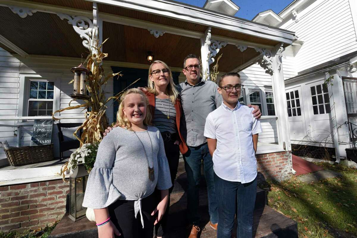 From left, Harmony, Sarah, John and Joshua Trop stand outside their historic home on Wednesday, Nov. 4, 2020 in Wynantskill, N.Y. Sarah and John Trop bought the home with a goal of restoring it. (Lori Van Buren/Times Union)