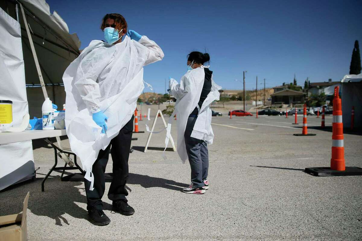 Jacob Newberry dons protective equipment at a COVID-19 state drive-thru testing site on Oct. 26 in El Paso.