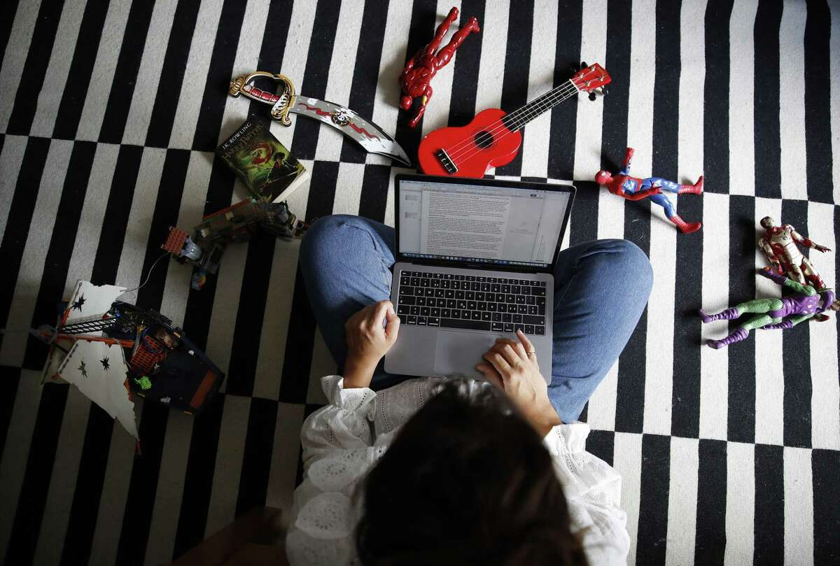 A woman works at an Apple Inc. laptop computer on the floor of a bedroom.