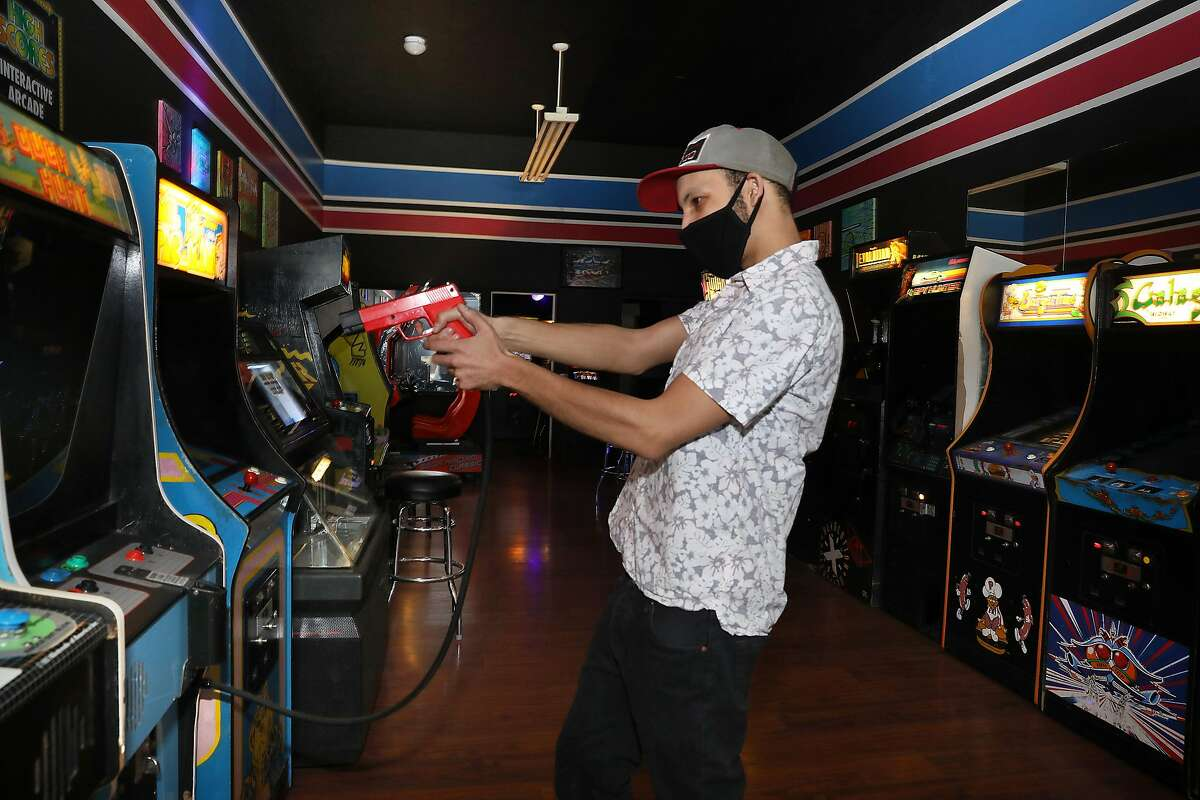 Manager Jonathan Williams shows a duck-hunting game at High Scores Arcade.