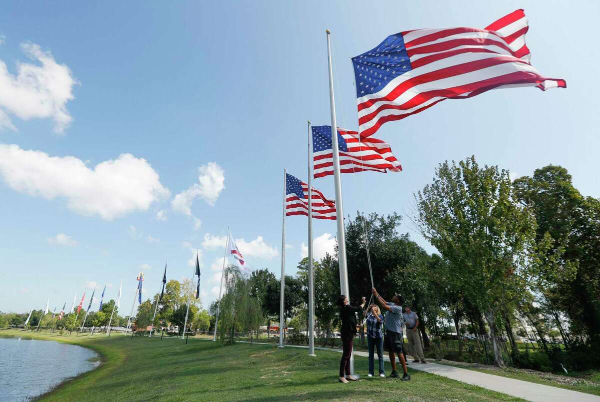 Volunteers help lower flags at the Montgomery County Veterans Memorial Park.