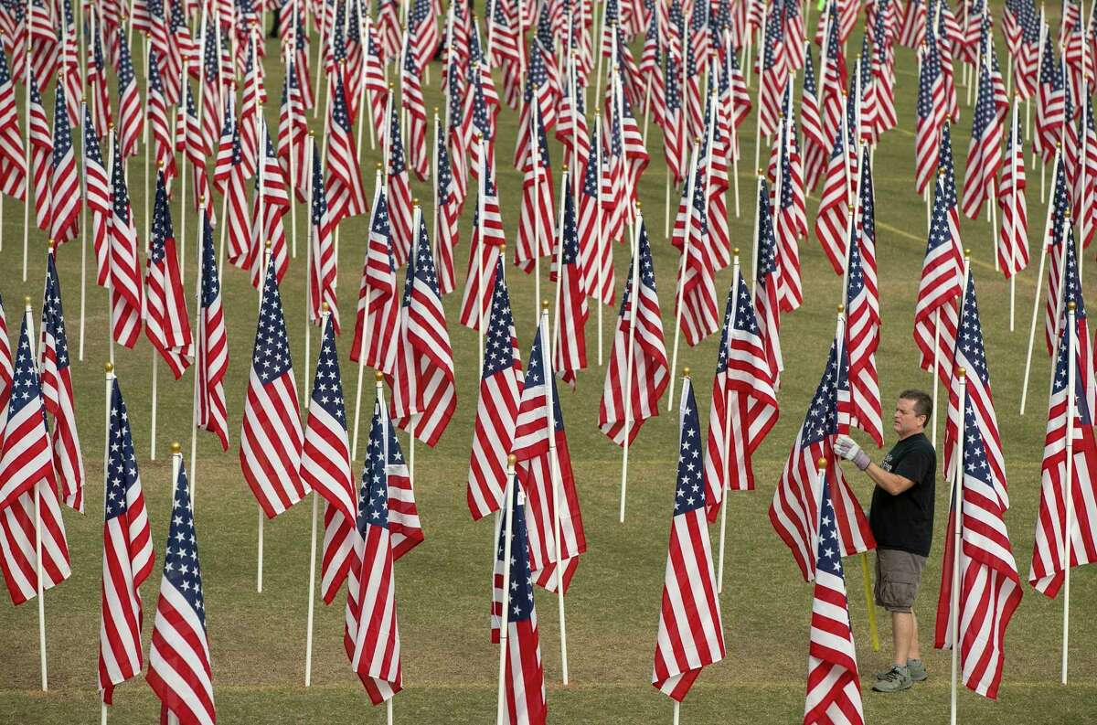 Joe Cuteri sets up a display at the annual Field of Honor at San Gabriel Park in Georgetown, Texas.
