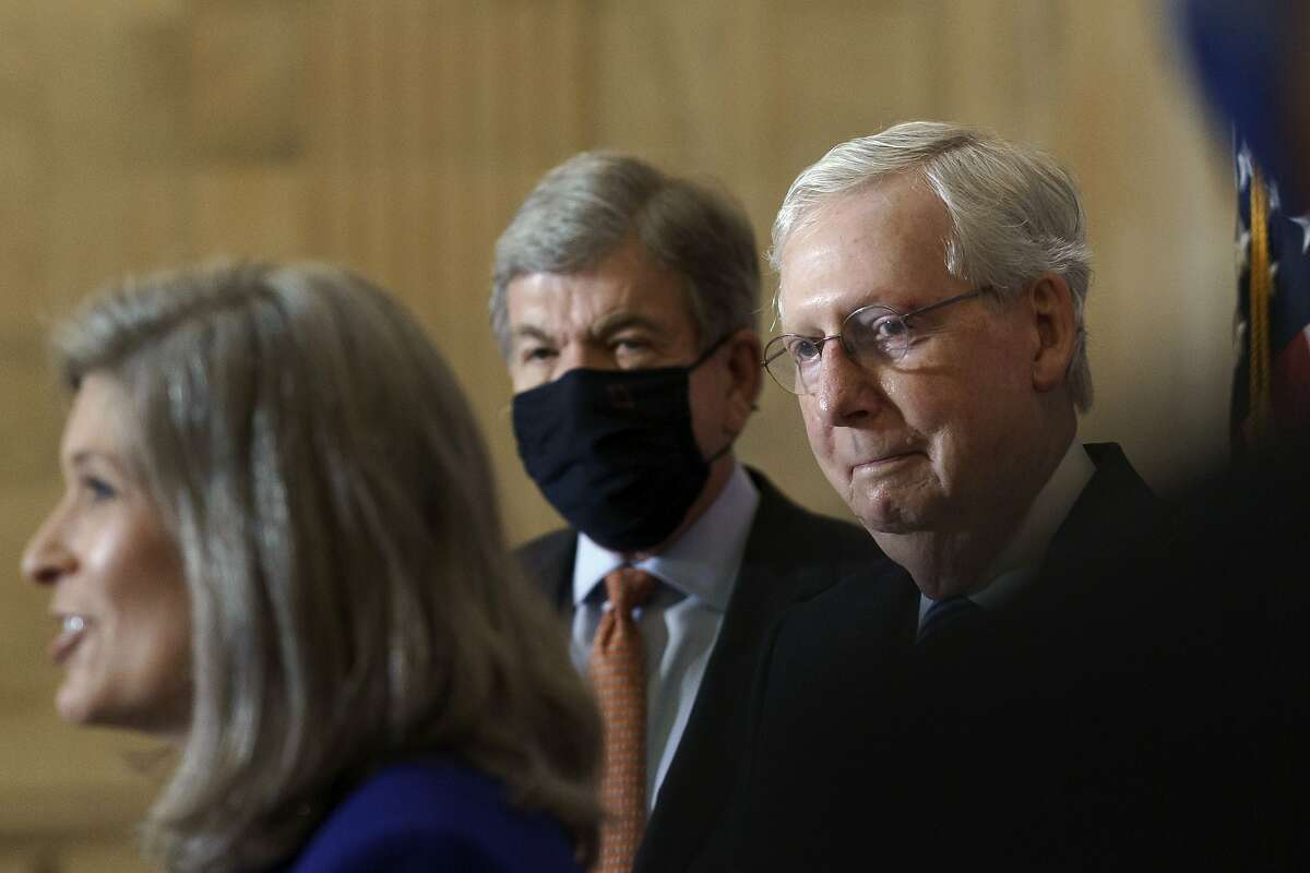 Senate Majority Leader Mitch McConnell, R-Ky., right, joined at center by Sen. Roy Blunt, R-Mo., center, smiles as Sen. Joni Ernst, R-Iowa, speaks after the Republican Conference held leadership elections, on Capitol Hill in Washington, Tuesday, Nov. 10, 2020. (AP Photo/J. Scott Applewhite)