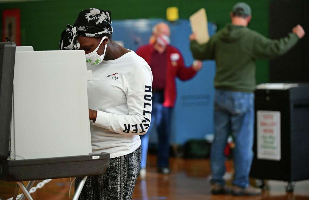 First-time voter Andrea Dixon casts her ballot at the polling station at West Rocks Middle School Tuesday, November 2, 20202, in Norwalk Conn.