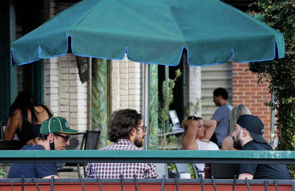 At a Houston coffee house, patrons sit on the patio, sipping coffee in the sun on Tuesday. Texas has reached more than 1 million cases of COVID-19.