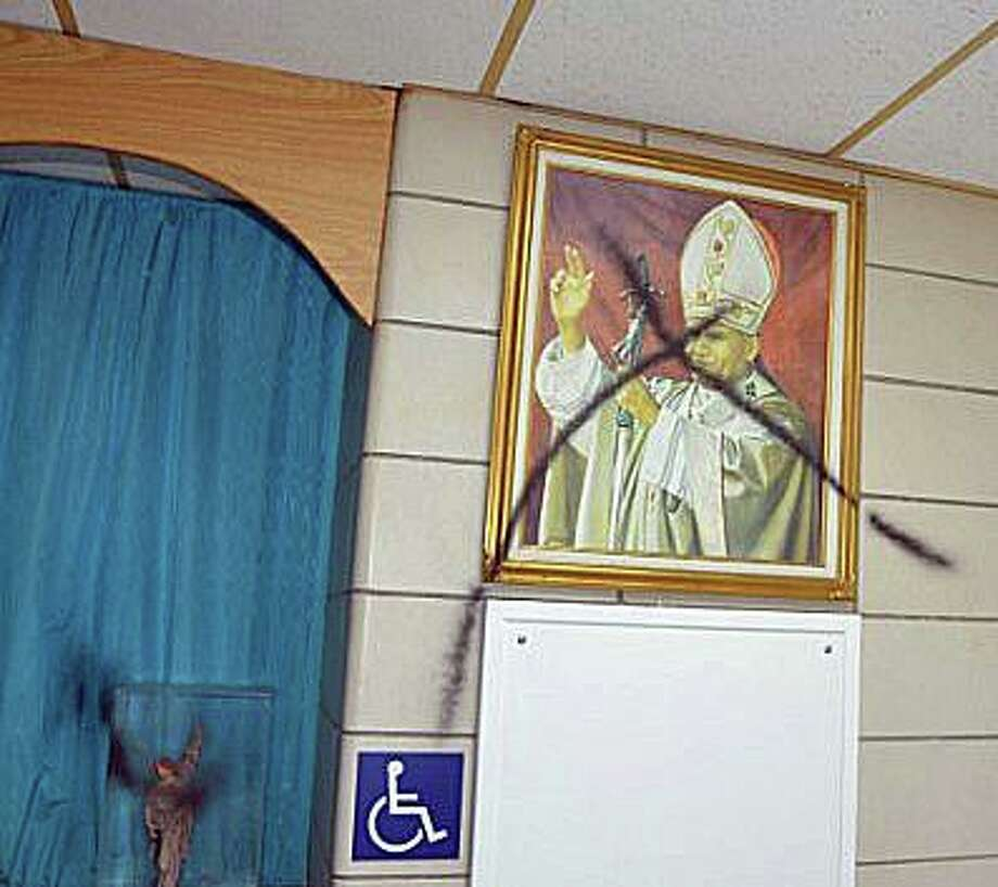 """Milford police are investigating a series of a series of burglaries and vandalism to the former Saint Gabriel Elementary School that has caused """"thousands of dollars in damage."""" Among the vandalism at the school was a defaced portrait of Pope John Paul II, who died in 2005. Photo: Milford Police Department Photo"""