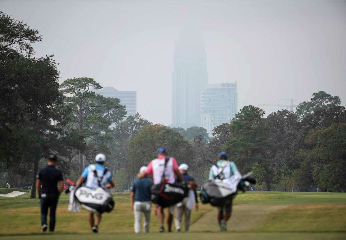 The Williams Tower is shrouded in fog as players walk down the fairway on the first hole at Memorial Park during the final round of the Vivint Houston Open.