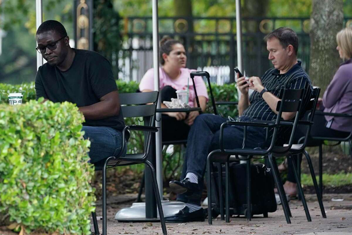 People sit outside in the Memorial area amid the COVID-19 pandemic Tuesday, Nov. 10, 2020 in Houston. Texas has reached more than 1 million cases of COVID-19, making it the first state in the country to pass this milestone.