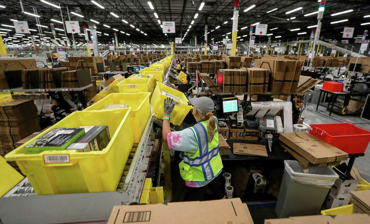 Amazon is hiring 2,800 seasonal workers in Houston as part of a national plan to fill 100,000 seasonal positions. A fulfillment center associate in the pack area, packs single-order boxes at the Amazon Fulfillment Center Hou2 in Houston.