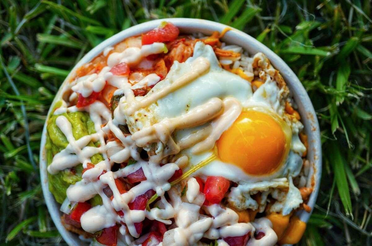 Kim BAP has seasoned rice, marinated beef bulgogi, spicy marinated chicken with onions, cilantro, cheese, and El Scorcho sauce.