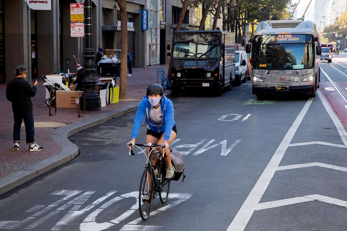 A cyclist bikes in front of a bus near the intersection of 4th and Market street in San Francisco, Calif. Friday, October 30, 2020. The Department of Public Works and the San Francisco Municipal Transportation Authority has been quietly telling stakeholders the past couple weeks that due to budget cutbacks, bicycles will now share a lane along with taxis, paratransit, and commercial vehicles, and Muni busses will use only the center lane instead of curbside stops. The city will save $40 million, but it will still cost $121 million and an additional $7 million for redesign. The plane came to a head at a meeting Tuesday, with city supervisors and bike and pedestrian advocates protesting the sudden change.