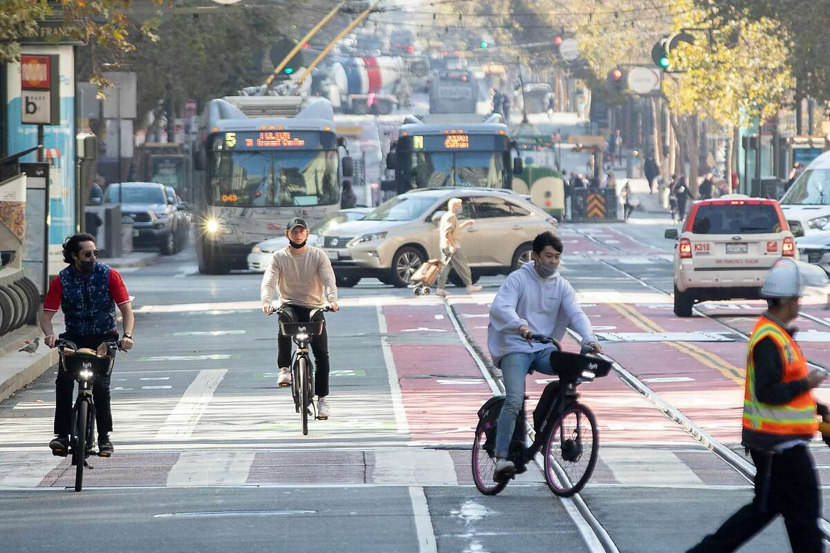 Cyclists move past buses and taxis near 3rd and Market street in San Francisco, Calif. Friday, October 30, 2020.