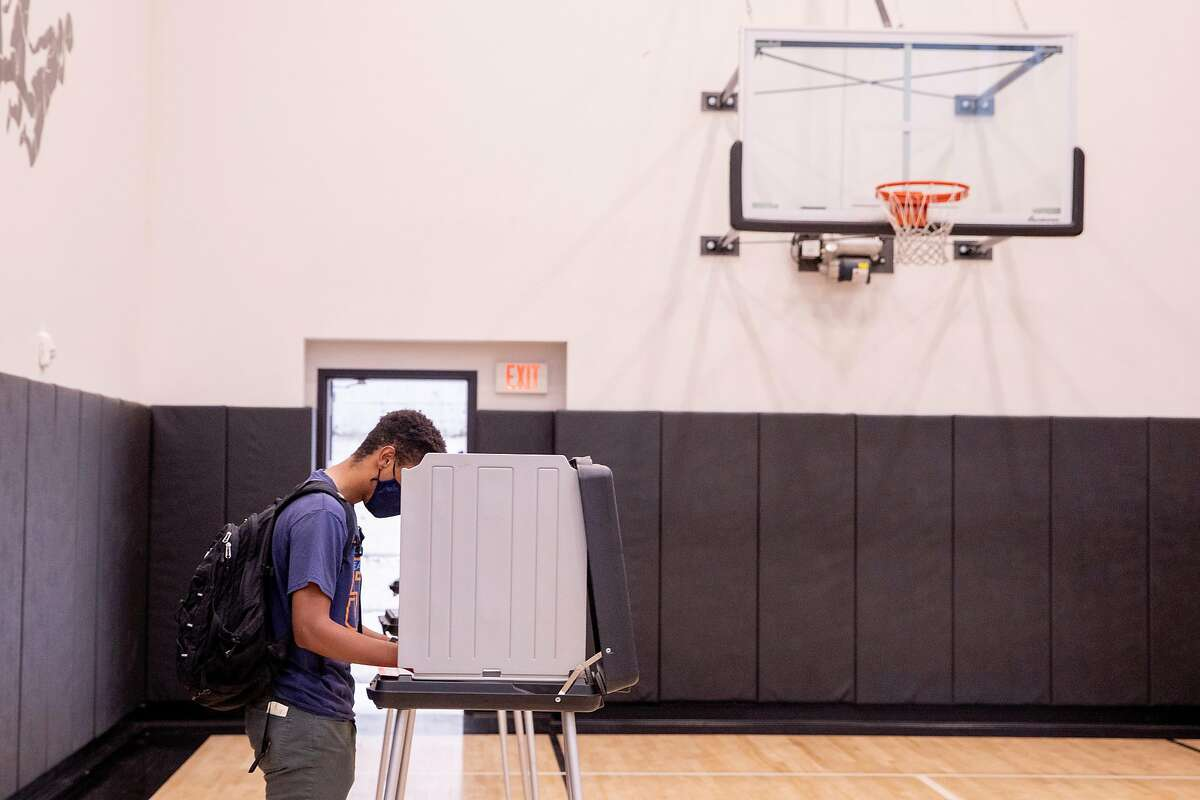 Thomas Namara, 24, wears a mask while casting his vote at a polling place inside an apartment building gym along Van Ness Avenue in San Francisco on Nov. 3.
